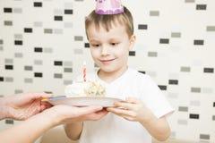 Kuchen für den Geburtstag des Kindes Junge hält Kuchen mit Kerze auf Geburtstag Mutter gibt Stück des Kuchens Stockfotos