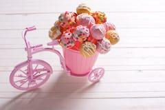 Kuchen knallt im dekorativen rosa Fahrrad auf weißem hölzernem backgroun Lizenzfreie Stockbilder