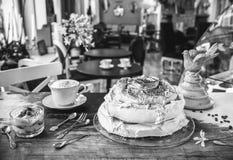 Kuchen-Meringe-, Nachtisch- und Lattekaffee auf einer Weinlesetabelle in einem Café in einem Retrostil lizenzfreie stockfotos