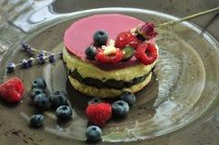 Kuchen mit Beeren und Lavendel auf Platte Stockbild
