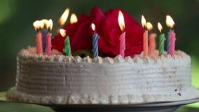 Kuchen mit brennenden Kerzen und Blumen stock footage