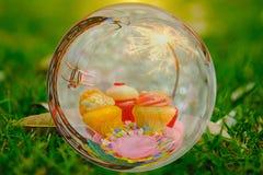 Kuchen mit drei Schalen, Spielzeugfläche und Parteiwunderkerze im Glaskugeleffekt mit Greem-Gartenhintergrund Stockbild