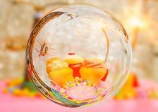 Kuchen mit drei Schalen, Spielzeugfläche und Parteiwunderkerze im Glaskugeleffekt mit unscharfem Farbhintergrund Lizenzfreies Stockbild