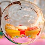 Kuchen mit drei Schalen, Spielzeugfläche und Parteiwunderkerze im Glaskugeleffekt mit unscharfem Farbhintergrund Stockbilder