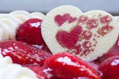 Kuchen mit Erdbeerherz-Formschokolade Stockfotos
