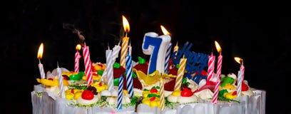 Kuchen mit festlichen Kerzen und Nr. 7 Stockbild