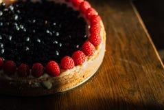 Kuchen mit Himbeeren und Blaubeeren auf dem Tisch lizenzfreie stockfotos