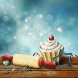 Kuchen, Nudelholz, Formen für das Backen, Süßigkeit und Serpentin auf dem Hintergrund bokeh Stockbilder