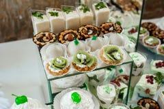 Kuchen, Süßigkeiten, Eibische, Früchte und andere Bonbons auf Nachtischtabelle Lizenzfreies Stockfoto