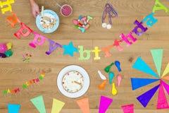 Kuchen-und Geburtstags-Dekorationen auf Holztisch Lizenzfreie Stockfotografie