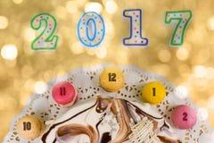 Kuchen und macarons als Uhr nahe Kerzen nummerieren 2017 auf hellem Lizenzfreie Stockfotos