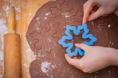 Kuchen verbreitete auf einem Countertop mit den die Hauptrolle gespielten Händen, Hände halten die Form, das Nudelholz liegt auf  lizenzfreies stockfoto