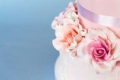 Kuchen verziert mit Blumen auf einem blauen Hintergrund Lizenzfreie Stockbilder