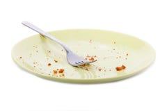 Kuchenkrumen und -gabel auf gelber Platte stockbild