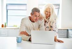 Kuchenna scena z spokojną parą patrzeje komputer Zdjęcie Stock