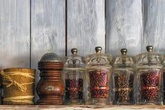 Kuchenni naczynia, ziele i pikantność na półce przeciw nieociosanej drewnianej ścianie, zdjęcia stock
