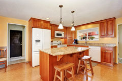 Kuchenny izbowy wnętrze z wyspą, drewnianymi gabinetami i granitu odpierającym wierzchołkiem, Zdjęcie Royalty Free