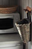 Kuchenny kosz na drewnianym wieszaku z mikrofalą na tle Zdjęcia Royalty Free