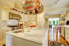 Kuchenny pokój z wyspy i obwieszenia garnkiem dręczy Zdjęcia Royalty Free