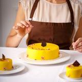 Kuchenny szef kuchni dekorujący żółty tort zdjęcia royalty free