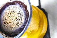 Kuchenny wnętrze - gotować kawę w żółtym indyczym turek na benzynowej kuchence Obrazy Royalty Free
