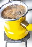 Kuchenny wnętrze - gotować kawę w żółtym indyczym turek na benzynowej kuchence Fotografia Royalty Free