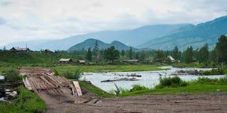 Kucherla village, wooden bridge across mountain river. Trekking in the Altai Mountains Royalty Free Stock Photos