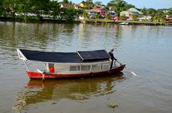 River ferry with boatman steers boat to landing jetty pier across Sarawak River Kuching Malaysia. Kuching, Malaysia - October 10, 2018: A river ferry boat with stock photo