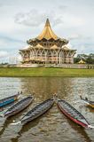 Kuching, Malaysia, Parliament building and longboats under the water festival regatta. royalty free stock photo