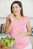 kuchnia ma ciężarną sałatkowej kobiety Fotografia Stock