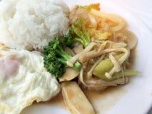 kuchnia tajska Smażący kolorowi warzywa, cebula, brokuły, pieczarka z mięsem w bielu talerzu z ryż i smażący jajko na bielu, zdjęcia royalty free