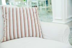 Kudde på den vita soffan i vardagsrum, tappningstil Arkivfoto