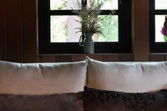 kudde, soffa och blomma bredvid fönster Arkivfoto