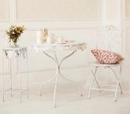 Kudde vitt rum för tappning med stol och tabellen med blommor, kaffekoppar och stearinljus Royaltyfria Foton