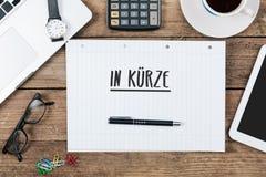In Kuerze deutscher Text für das Kommen bald auf Notizblock an Büro-DES Stockfotografie