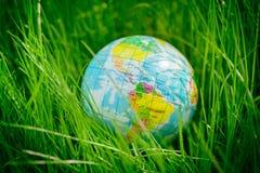 Kugel auf Gras Tag der Erde, Umweltkonzept Lizenzfreies Stockfoto