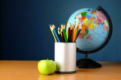 Kugel, Bleistifte und Apfel auf der Tabelle Lizenzfreie Stockbilder