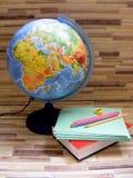 Kugel, Bleistifte und Bücher auf Bambushintergrundkonzeptbild Lizenzfreies Stockfoto