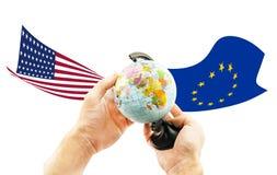 Kugel in den Händen auf einem Hintergrund von Flaggen der EU und der US Stockbild