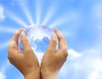 Kugel in der menschlichen Hand gegen Sonne und blauen Himmel. Lizenzfreie Stockfotos