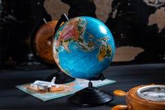 Kugel mit einem Barometer und einer kleinen Fläche auf dem Hintergrund einer schwarzen Weltkarte stockfotos