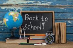 Kugel, Wecker, Bleistifte, Kreide, Bücher und Schiefer mit zurück zu Schultext Lizenzfreie Stockbilder