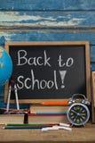 Kugel, Wecker, Bleistifte, Kreide, Bücher und Schiefer mit zurück zu Schultext Lizenzfreie Stockfotos