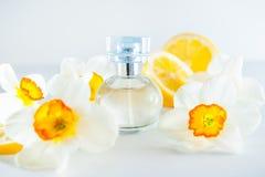 Kugelförmige Parfümflasche umgeben durch frische Narzissenblumen und die Zitronenscheiben lokalisiert auf weißem Hintergrund Gelb Lizenzfreie Stockbilder
