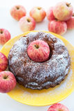 Kugelhopf apple cake on  yellow plate with red apples around Royalty Free Stock Image