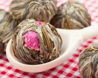 Kugeln des grünen Tees mit Blumen im hölzernen Löffel Stockbild