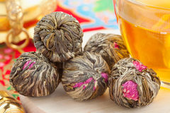 Kugeln des grünen Tees mit Blumen, Teecup Stockfotografie