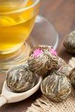 Kugeln des grünen Tees mit Blumen, Teecup und hölzernem Löffel Lizenzfreies Stockfoto