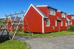Kuggar för luft-torkade fisk och hus av byinvånare, Svolvaer, Norw Arkivbild