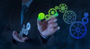 Kugghjul för affärsmanhandattraktioner till framgångbegreppet Arkivbild